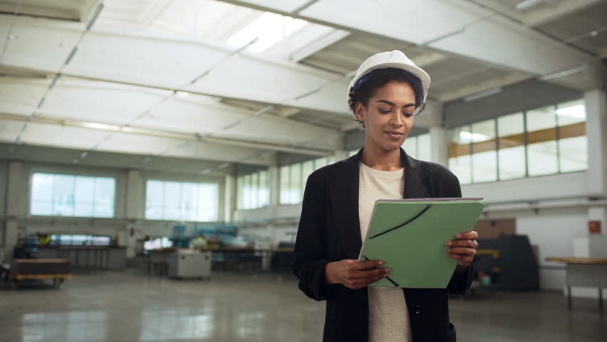 Portrait of african american happy woman in helmet and suit holding documents and presenting production of international company in large factory slow motion