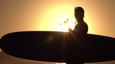 SLOW MOTION CLOSE UP SILHOUETTE: Cheerful young surfer girl standing in shallow ocean water, holding longboard surfboard in hands and doing the shaka surfers sign at golden summer evening sunset