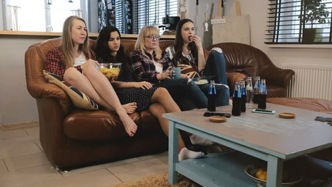 Beautiful female friends discuss drama movie on TV. Young emotional girls watching sad romantic film 4K slow motion.