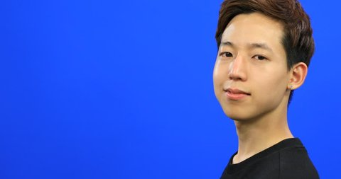 Asian young man turning to camera and smiling on blue screen