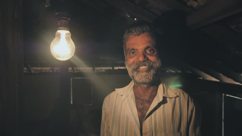 A poor man smiles after a tungsten light bulb slowly turning on or brighten up in old rural house. A happy farmer smiling after a light bulb turn on and receiving electricity for the first time.