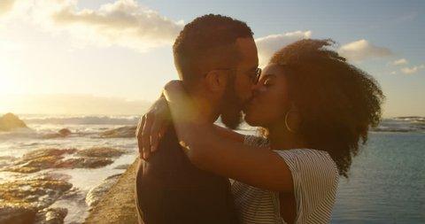 Couple kissing each other on the beach at dusk 4k