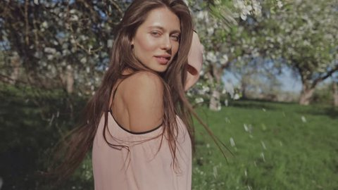 Beauty young woman enjoying nature in spring apple orchard, Happy Beautiful girl in Garden with blooming trees. Slow motion video shooting by handheld gimbal