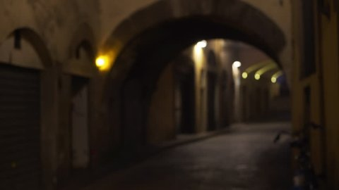View of narrow European street with archways. Low lighting alley with arched ceilings in Europe