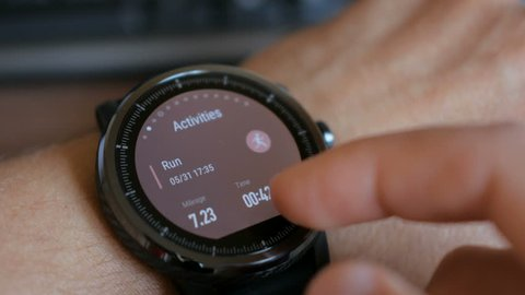 Young man making gestures on a wearable smart watch computer device, smartwatch closeup.