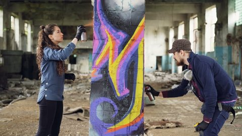 Two skilled graffiti artists bearded guy and attractive young woman are working together in abandoned warehouse decorating old column with abstract image.