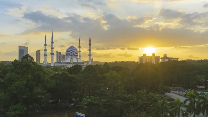 High Angle Dramatic Sunset Time Lapse at Sultan Salahuddin Abdul Aziz Mosque. Shah Alam, Malaysia. Day to Night. Pan down motion timelapse.