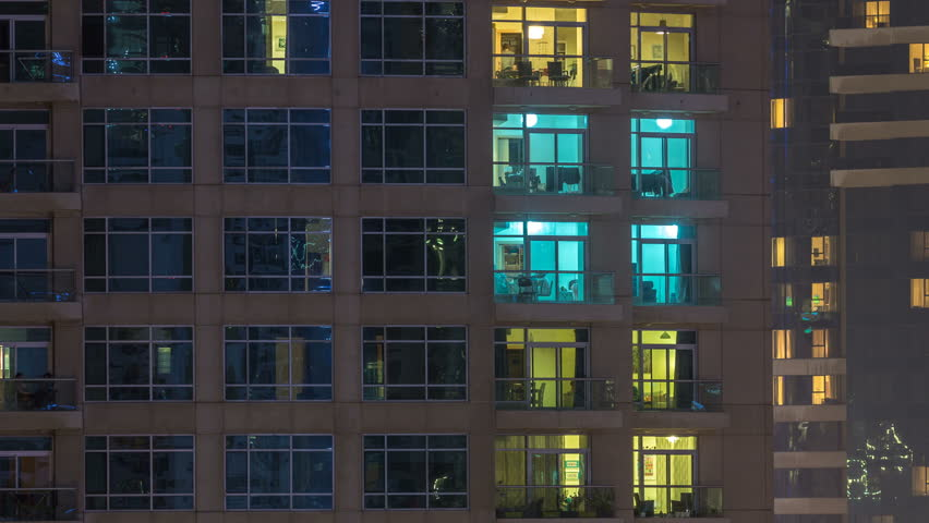 Windows of the multi-storey building of glass and steel lighting inside and moving people within timelapse. Aerial view of modern residential skyscrapers in Dubai marina. Zoom out   Shutterstock HD Video #1011840509