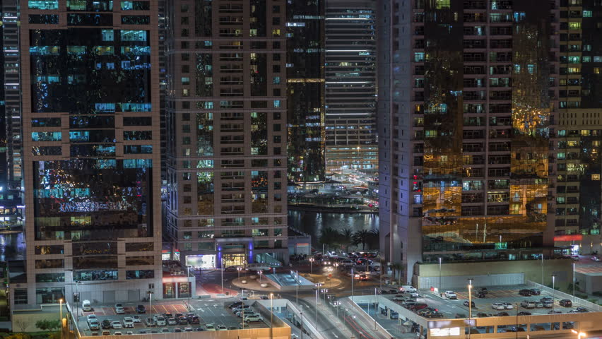 Aerial view of Jumeirah lakes towers with illuminated skyscrapers night timelapse with car parking and traffic on sheikh zayed road and metro line. Rooftop view from Dubai marina