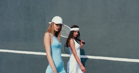 Portrait of two young Caucasian teen models wearing fashionable tennis dress, passing by and looking into camera, summer sunny day outdoors. Fashion portrait shoot