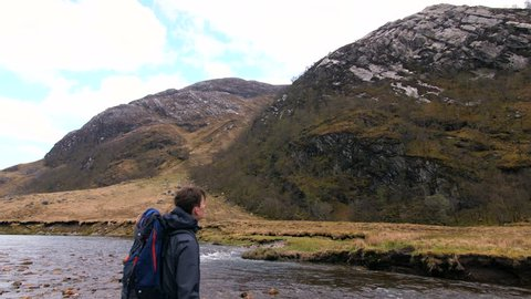 4K Young traveller in Scottish Highlands. Student back pack nature path trekking through mountains and lakes. A natural marsh and water landscape with a British tourist exploring rural Scotland.