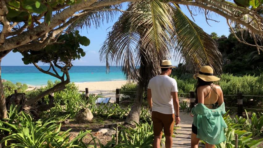 Couple Walking Down to Beach of Tulum Mexico Tracking Shot | Shutterstock HD Video #1011896579