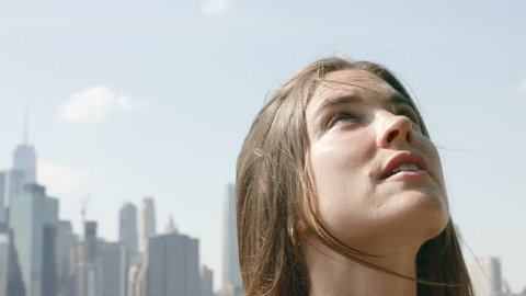 A portrait of a beautiful young woman looking up to the sky, 4K slow motion on a windy day outside in New York City, NY