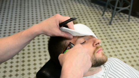 Men's hairstyling and haircutting in a barber shop or hair salon. Grooming the beard. Barbershop. Man hairdresser doing haircut beard adult men in the men's hair salon. Hairdressers in the workplace