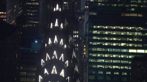 New York City - Circa 2018: Aerial night time NX establishing shot stock video overhead midtown manhattan. Close up Chrysler building reveal busy streets and lights from times square in background