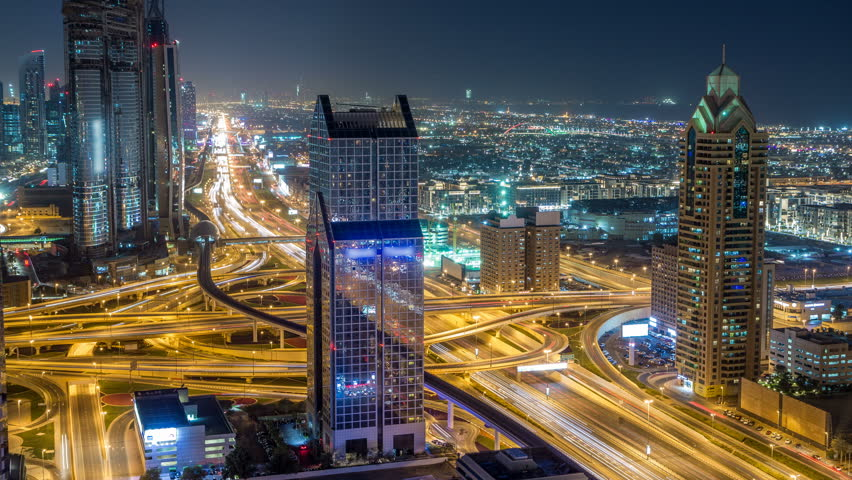 Night traffic on a busy intersection on Sheikh Zayed highway aerial timelapse. View from rooftop in Dubai downtown with modern skyscrapers #1011916409