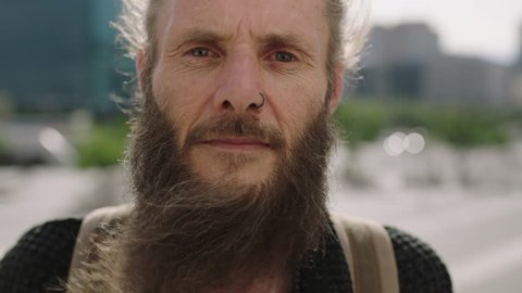 close up portrait of serious mature hippie man looking pensive at camera staring intense in urban city background authentic eccentric