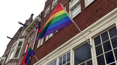 "AMSTERDAM,NETHERLANDS-1 MAY,2018:Rainbow ""gay pride"" flag waving on house facade in center of Amsterdam city.Club for homosexual people in Holland."