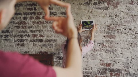 Pretty asian woman is choosing place for framed photograph on brick wall while her boyfriend is making frame shape with his fingers and looking at her, hands in foreground.
