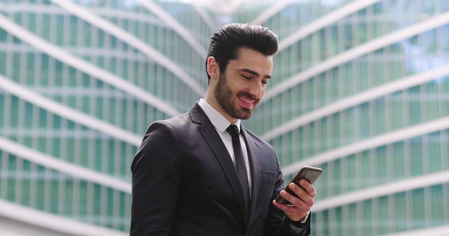 An business man in a suit and tie is happy and smiling while sending messages, working emails or calling using the phone. Concept of: technnology, network, success. | Shutterstock HD Video #1011947519