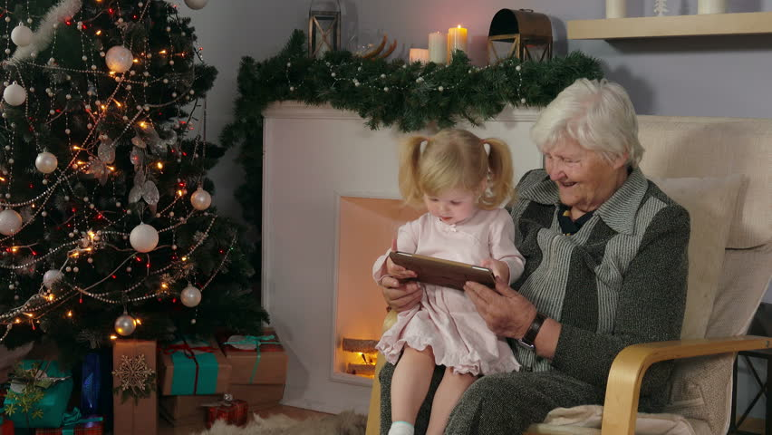 Baby playing on the tablet while sitting on the lap of her grandmothe