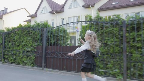 Little funny schoolgirl in school uniform and briefcase on his shoulders walking around the area. In the hands of the girl rainbow spinner. Steadicam shot