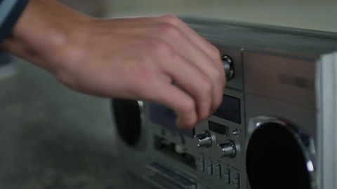 Teenage boy putting tape recorder on the floor and turning it on to listen to music, close up shot of tape recorder