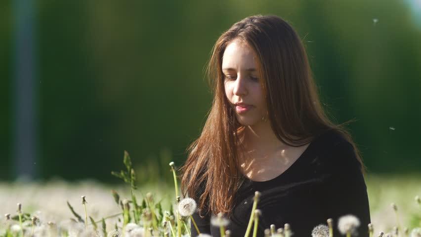Cute happy girl blowing dandelion in a meadow of dandelions
