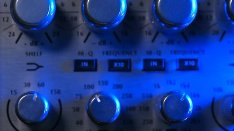 Adjustable handles on the compressor panel in professional recording studio. Blue neon light. Sound mixing concept. Dolly shot. 4k.