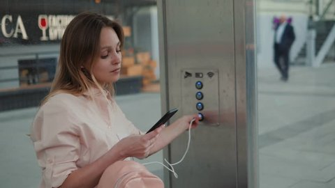 Young woman student girl charging mobile phone, outdoors on bus train underground stop station, modern city while waiting bus transportation, energy electricity for devices
