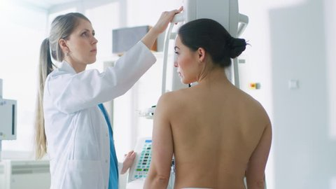 In the Hospital, Mammography Technologist / Doctor adjusts Mammogram Machine for a Female Patient. Modern Technologically Advanced Clinic with Professional Doctors.  Shot on RED EPIC-W 8K Camera.