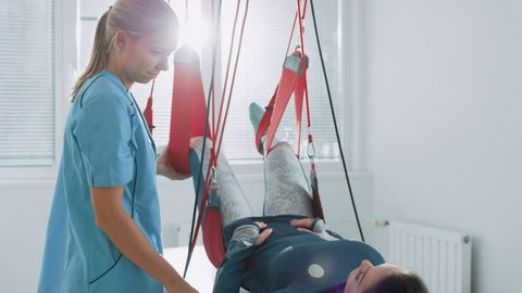 Physiotherapist Assists Female Patient with Trauma, Undergoing Rehabilitative Physiotherapy on a Special Suspension Rope System. Relieving Back Pain.  Shot on RED EPIC-W 8K Helium Cinema Camera.