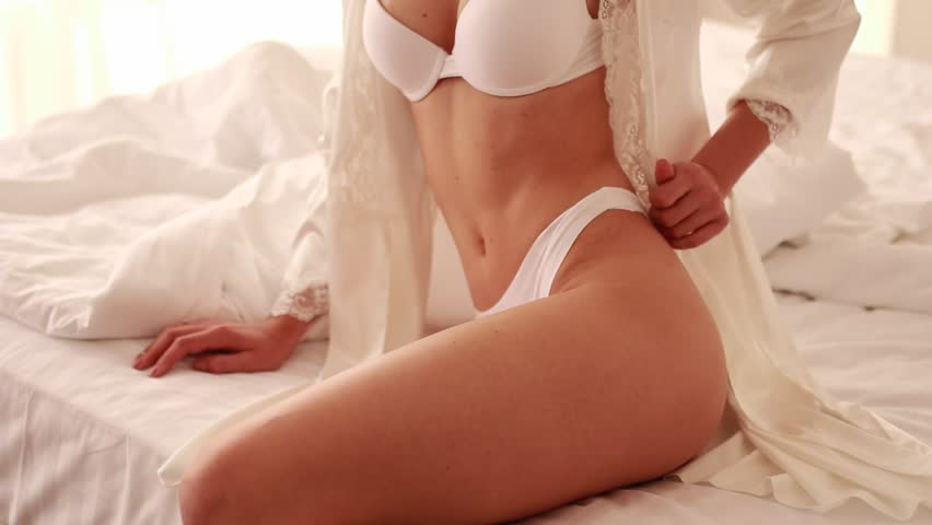 Young woman in white lingerie and peignoir sits on bed and dresses.