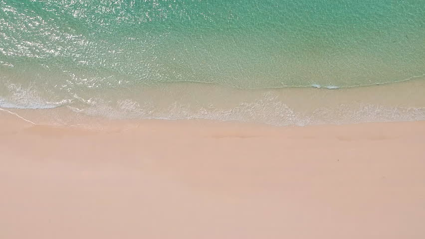 Aerial view of clear sand beach and sea. Ocean surface texture, Top view sea waves flying over tropical clear sandy beach and waves, background for movie credit   Shutterstock HD Video #1012077299