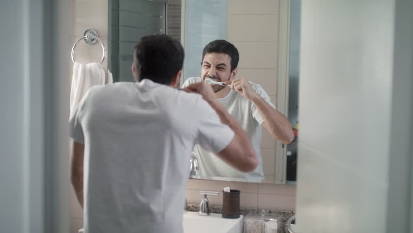 Young hispanic man late for work, grooming fast in bathroom. White metrosexual man brushing teeth with strength, looking at mirror trying to whiten them.
