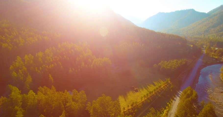 Aerial UHD 4K view. Mid-air flight over fresh mountain river and meadow at sunny summer morning. Green trees and sun rays on horizon. Rural dirt road below. #1012123319