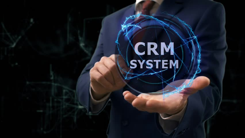 Businessman shows concept hologram CRM system on his hand. Man in business suit with future technology screen and modern cosmic background