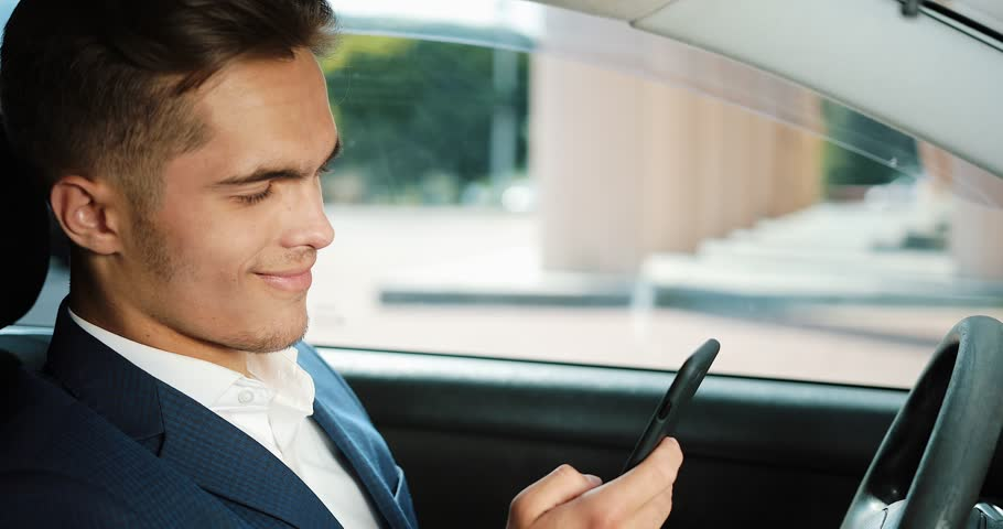 Young handsome businessman using mobile phone in the car. Happy young man succeeds and writes a message. The concept of communication, successful business, mobile technology | Shutterstock HD Video #1012125359