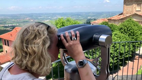 Woman peering through binocular view finder at the beautiful church of and surrounding panorama of Diano d'Alba in Piedmont region in Northern Italy. Camera follows her view on the church and the