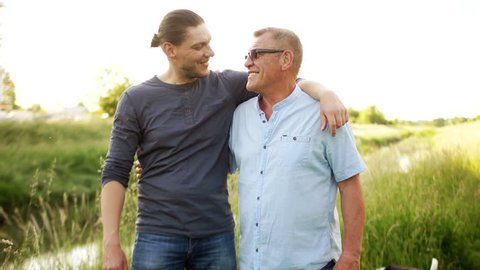 Two generations of one family, father and son. Male friendship. Father's day. Men stroll along the river bank, hug each other tightly