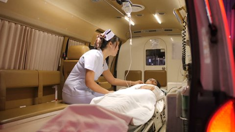 Female paramedic treating patient in ambulance.