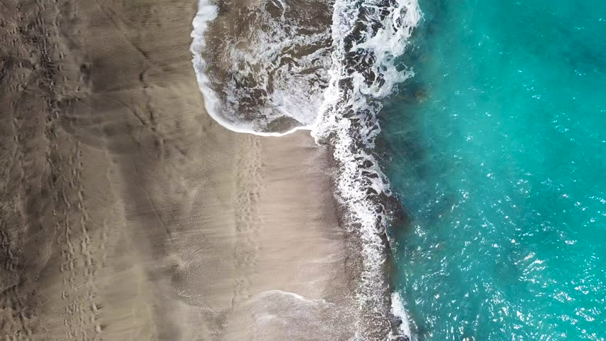 Top view of a deserted beach. Coast of the island of Tenerife. Aerial drone footage of sea waves reaching shore