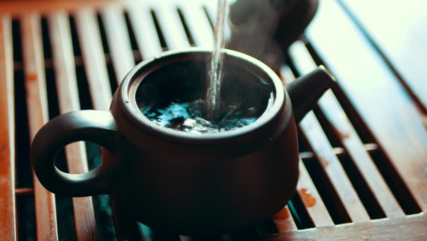 Chinese tea ceremony with puerh tea, Brewing black Shu Puer in pot from Ixin clay, boiling water pours into kettle, close up with selective focus