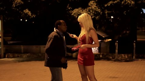 Sexual harassment. Sexy pretty blonde girl in red dress and afro american
