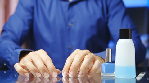 Man in blue shirt file long nails in slow motion 4K. Static medium shot of headless person hands in focus while manicuring with a nail file. Nail polish remover besides.