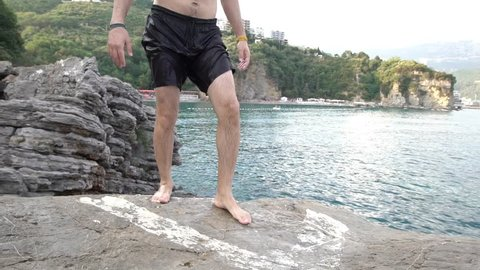 SLOW MOTION: Man jumping from cliff to sea. Young athletic male does jumps from a rock and does a backflip before diving into the sea.