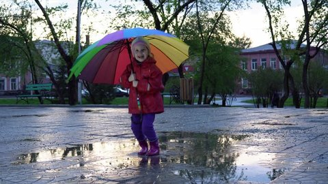 A cute little girl with a colorful umbrella is jumping and dancing in the puddles in the park at sunset.
