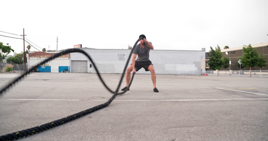 Athletic male working out in an empty parking lot. Slow Motion. | Shutterstock HD Video #1012218479