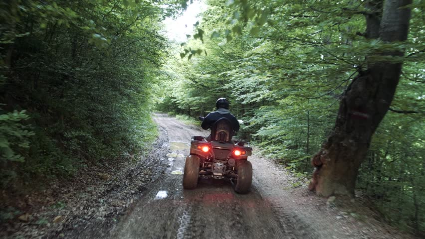 Man driving quad bike HD slow-motion video. All-terrain vehicle riding ATV in forest. Four-wheeler quadricycle transport and extreme sport.
