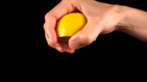 Super slow motion squeezing lemon juice. Fornt view.